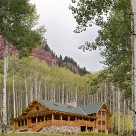 Luxury log home with wrap around porches, three story bay window with copper trim and river rock patio set in aspen forest below red rock cliffs.