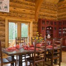 Dining room table and chairs in handcrafted log home with views through french doors to forest. Custom red china hutch in corner.