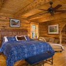 Luxurious bedroom in handcrafted log home with sitting area through log archway. Shiny hardwood floors, king size bed with ceiling fan above.
