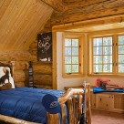 Walkout bay in luxury log home bedroom with log bed and blue comforter.
