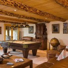 Pool table in rustic basement gameroom, handpeeled log beams accent the pine ceiling.