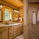 Walk in stone shower in handcrafted log home bathroom with custom cabinetry and pine window trim.