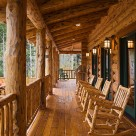 Cozy covered porch with log beams, log railings and log rocking chairs with views to Colorado aspen forest.