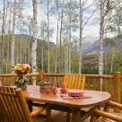 Log table and log chairs set on large deck with log railings with aspen trees in the background.