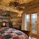 Master bedroom in luxury log home with stine fireplace in corner, exposed log beams in ceiling and views of Colorado mountains through french doors.