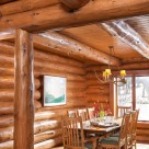 Photo of handcrafted log home dining room with handmade dining table, log post and log beams supporting ceiling with pine T&G boards.