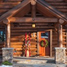 Cloe up photo of log home entry with stone pillars supporting log post and beam with Christmas wreath on door.
