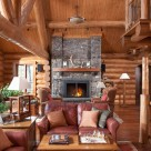 Photo of handcrafted log home great room with Chief Cliff stone fireplace, red leather chairs and cathedral ceilings with log truss.