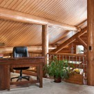 Open loft in handcrafted log home with antique desk and chair. Log truss, posts and exposed beam with t&g pine ceiling.