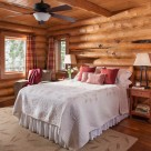 Handcrafted log home bedroom with wood floors, area rug and cozy bed.