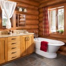 Custom log home bathroom with slate floors, white antique tub, alder cabinets and sconce lighting.