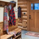 Log home mudroom with Alder door, slate floor, wood bench and coat rack with colorful scarves.