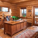 Log home office space with Oak desk, green lamps, wood floors and views through window to Flathead Lake, Montana.