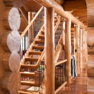 Cloes up photo of log posts and beam with log staircase and custom metal railings.