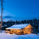 Stunning twilight photo of dovetail log cabin in winter.