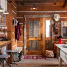 Interior photo of antique wood door in chink style log cabin.