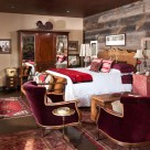 Red velvet chairs in bedroom with reclaimed wood on walls, antique rugs and furnishings.