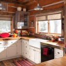 Kitchen in chink style dovetail log home with white cabinets and wood counter tops.
