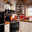 Close up photo of faux antique cook stove and barnwood cabinets.