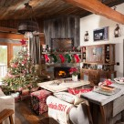 Living room of log cabin decorated with Christmas tree and stockings.