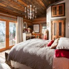 Bedroom of chink style log cabin with cozy bed, reclaimed wood ceiling, crystal chandelier and view to snowy forest through french doors.