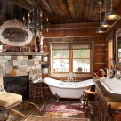 Clawfoot tub next to stone and wood fireplace in bathroom of handcrafted dovetail log cabin.