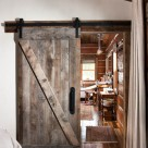 Sliding barnwood door with black metal hardware in chink style log cabin.