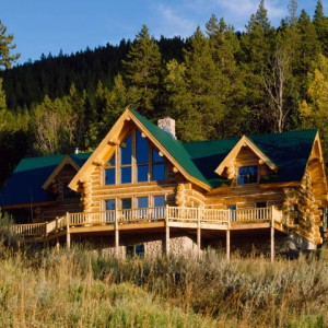 Exterior of handcrafted log home with green metal roof