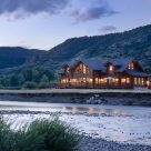 Twilight photo of magnificent handcrafted log home with river in foreground and Colorado mountains beyond.