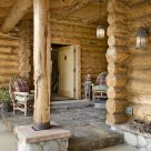 Photo of Scandinavian full scribe log home entry porch with stone patio and wicker chairs.