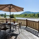 Exterior, horizontal, table setting on deck looking out to view of the Yampa river, Meyer residence, Milner, Colorado; Montana Log Homes