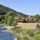Photo of Massive log home on Yampa river in Colorado with three car attached garage, multiple roof lines and green field in foreground.