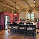Photo of log home kitchen with hardwood floors, red cabinets, exposed log beams with pine ceiling.