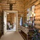 Photo of handcrafted log home entry door with patio beyond and log staircase to left.