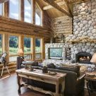 Photo of handcrafted log home great room with river rock fireplace and large windows with views to river and forest beyond.
