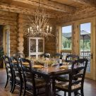 Photo of handcrafted log home dining room with dark wood table and chairs, antler chandelier and french doors with view of Colorado river and forest beyond.