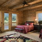 Photo of handcrafted log home bedroom with two queen beds with red comforters and views through large widows and glass door to river and forest.