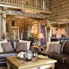 Photo of log home living room with leather sofas, custom coffee table and character log posts supporting log catwalk with log railings.