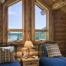 Close up photo of log home bedroom with twin beds, rustic nightstand and trapezoid windows in log gable.