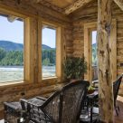 Photo of custom log home sitting room with wicker chairs and view through large pine trimmed windows of river and forest.