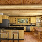 Rendering of log home kitchen with hardwood floors, exposed log beam ceiling, pine cabinets and dark granite countertops.