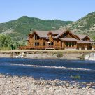 Photo of luxury log home viewed from across Yampa river with mountains in background.