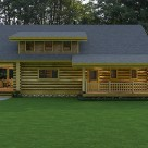 Side view of handcrafted log cabin with covered porches and shed dormer.