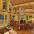 Living room with river rock fireplace in handcrafted log cabin.