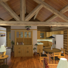 Interior rendering of handcrafted log home kitchen and dining rooms with log truss supporting roof purlins and pine ceiling.