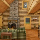 Rendering of log home living room with stone fireplace, green couch and breakfast bar.