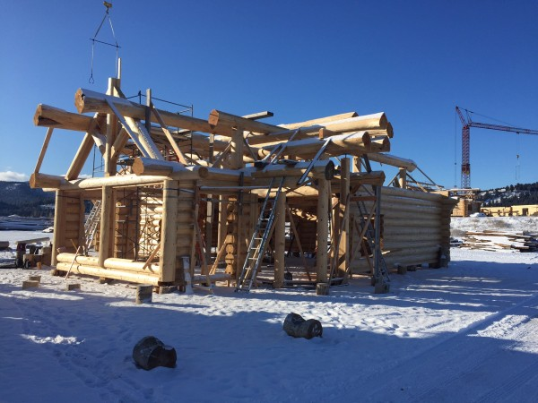 A custom log truss tops two large window openings in this handcrafted log shell.