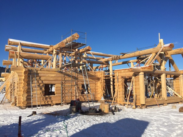 Snow doesn't stop the completion of this Scandinavian full scribe log home package.