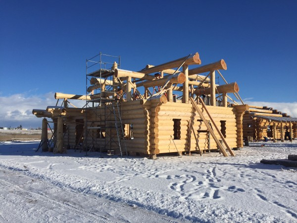Snow covers the ground, but construction is till underway to complete this handcrafted log package.