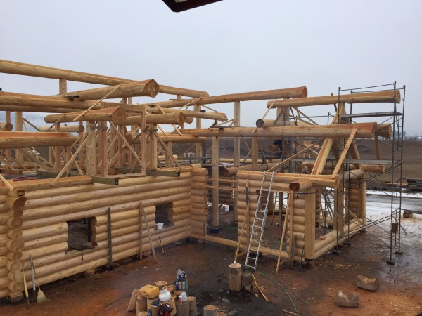 With scaffolding and ladders the log roof support system is completed for this handcrafted log package.